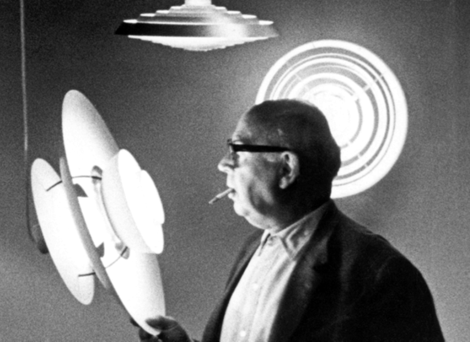 Poul Henningsen is holding a PH 5 pendant lamp and has a cigarette in his mouth